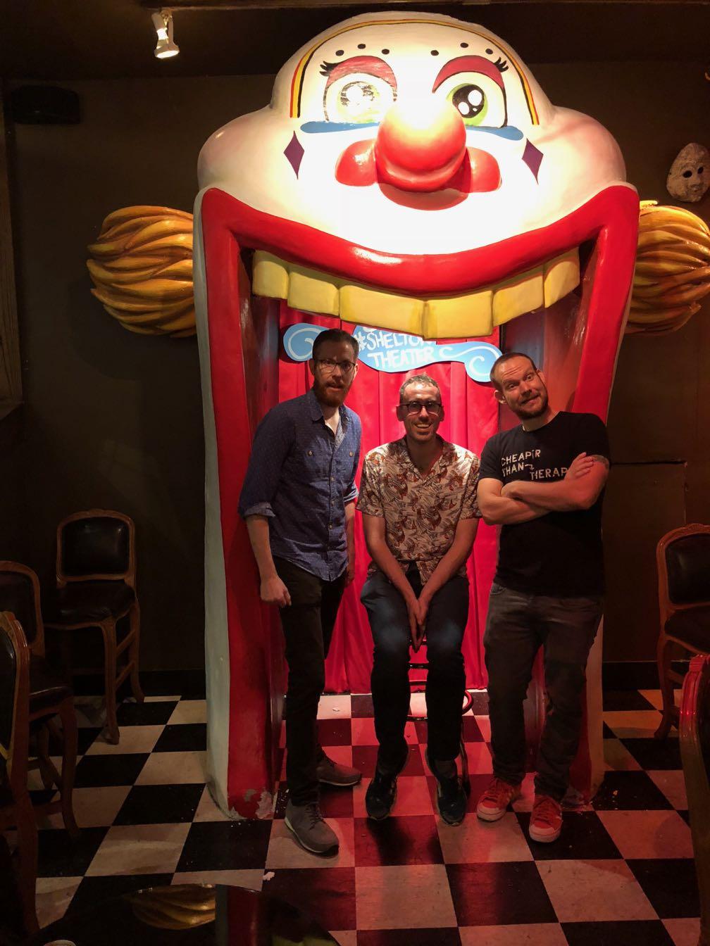 Scott Simpson, Ben Jennings, and Jon Allen standing inside a bizarre clown in a dimly lit theater lobby.