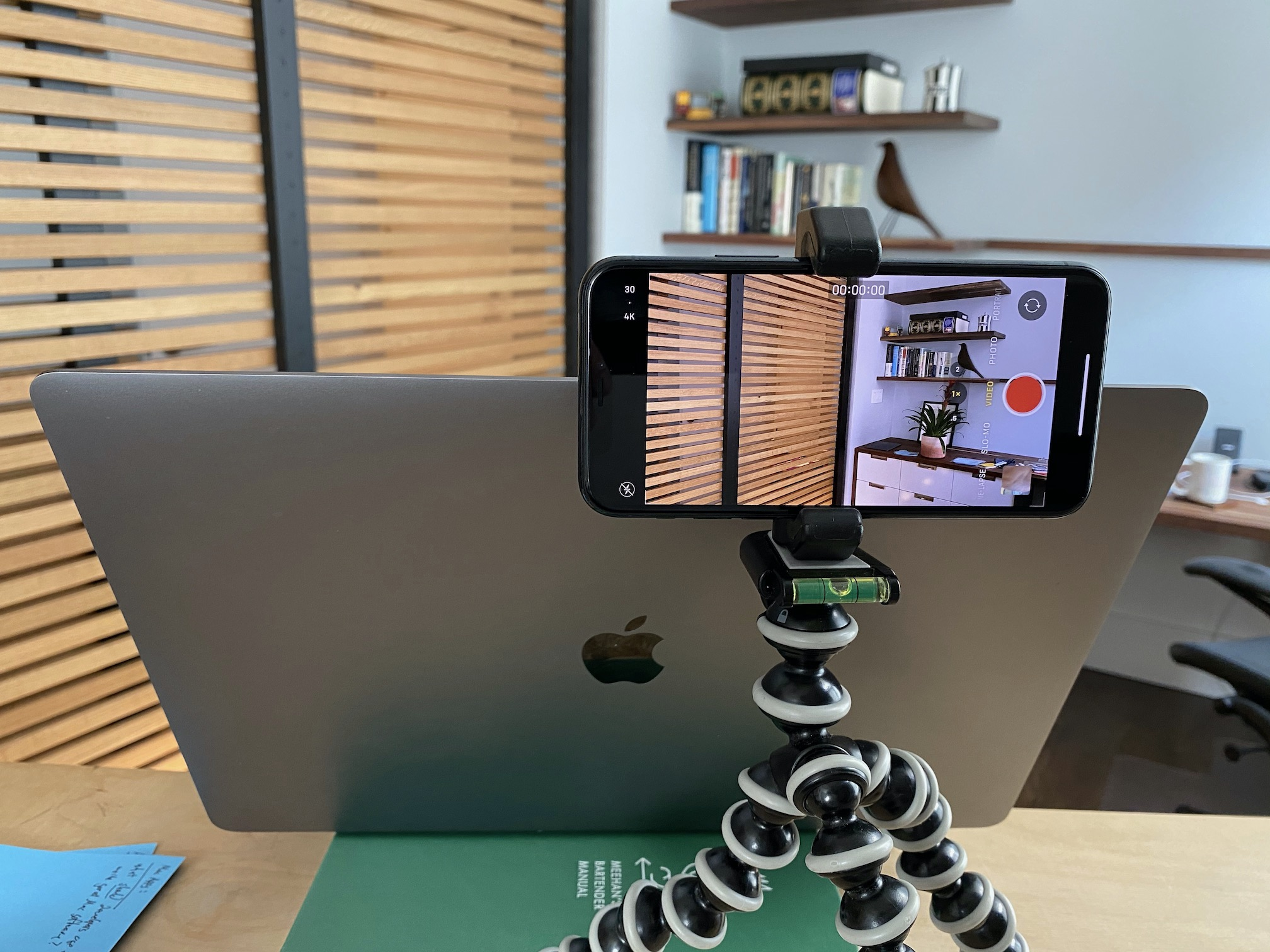 A photo of the camera setup in my office, showing an iPhone mounted on a tripod behind and slightly above an open MacBook Pro.