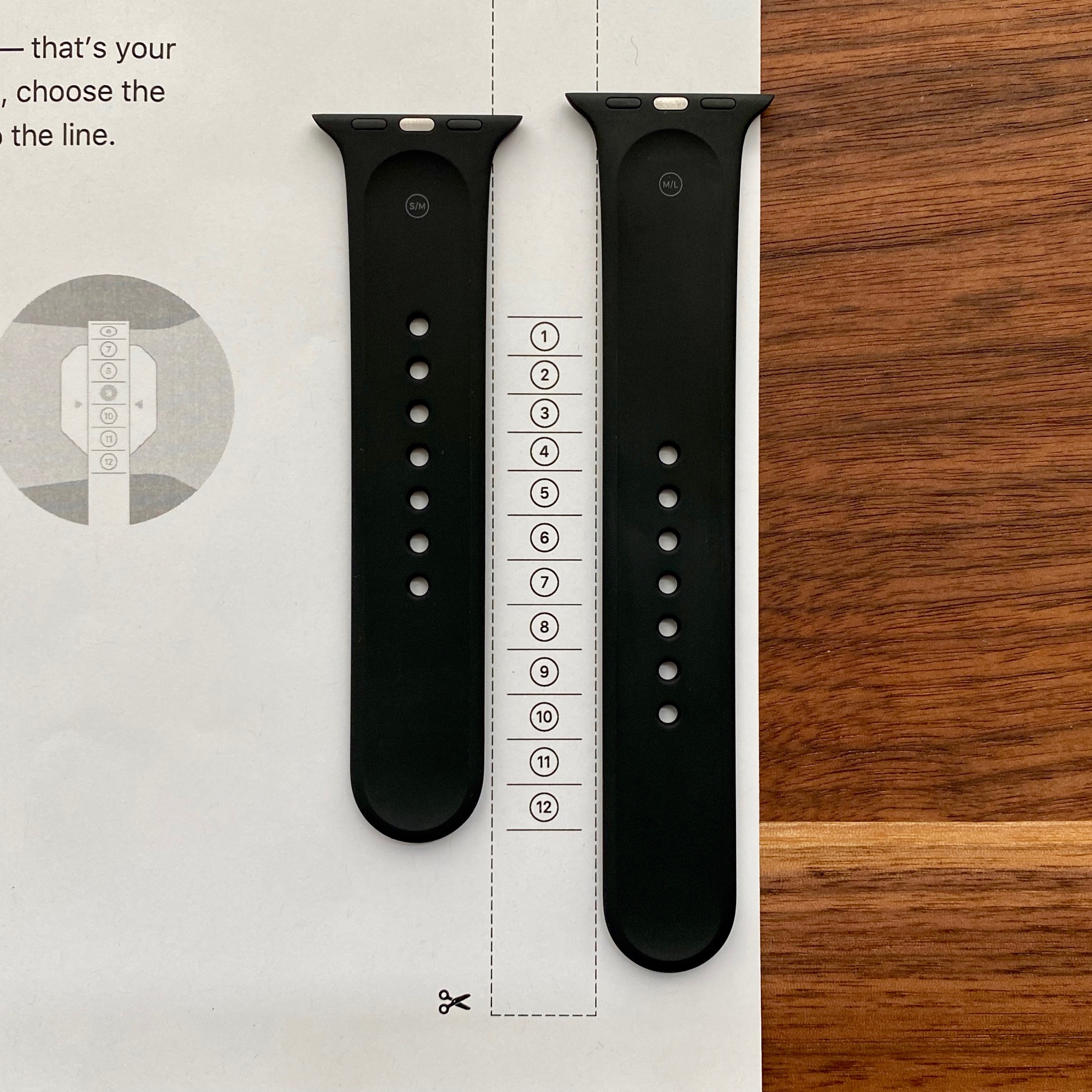 Two black 40mm Apple Watch Sport Bands, one S/M and one M/L, laid next to a printout of Apple's PDF sizing tool for Solo Loop bands.