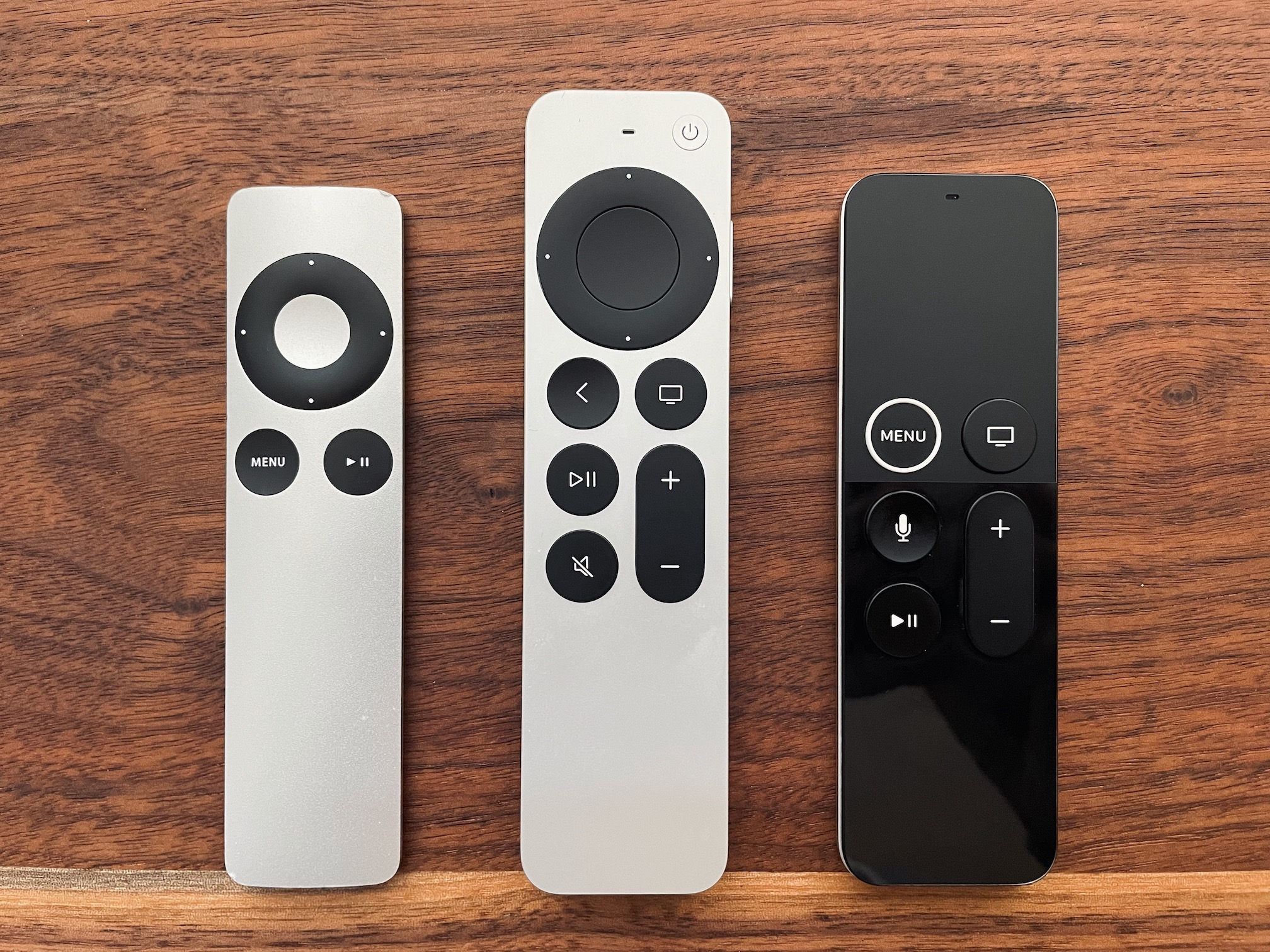 Three generations of Apple TV remotes, side-by-side.